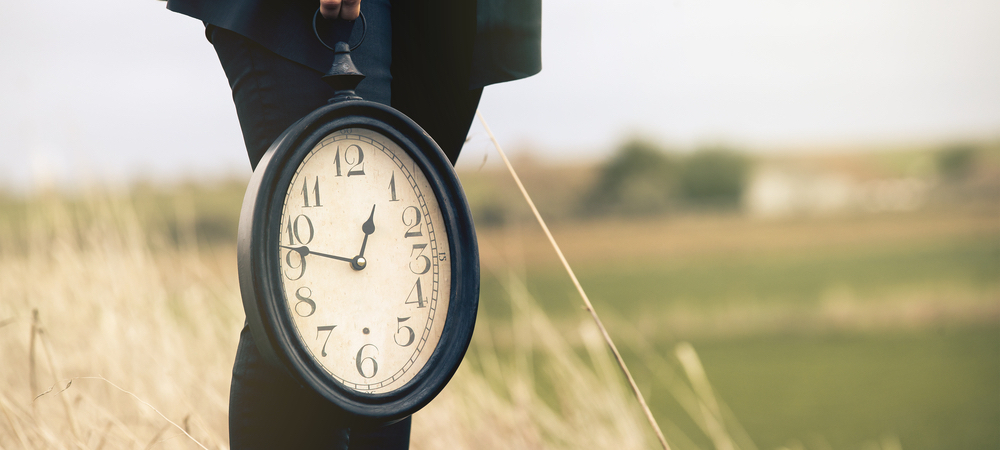 man holding a clock in a field